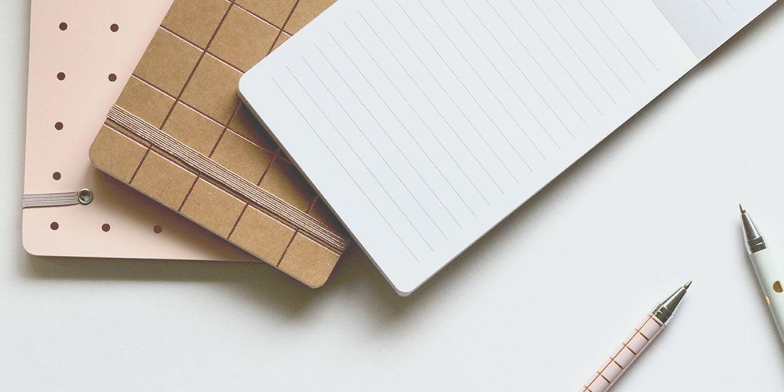 Briefing schreiben: Notizblöcke und Stifte liegen auf dem Schreibtisch