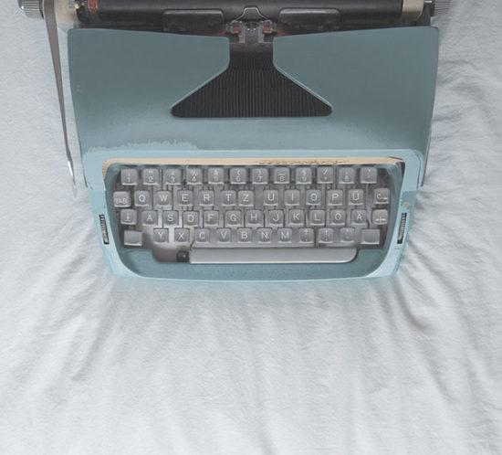 Grüne Schreibmaschine auf weißem Untergrund